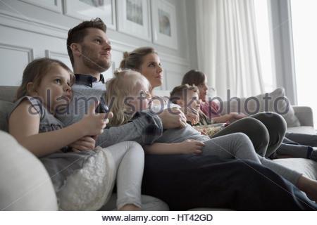 Junge Familie vor dem Fernseher im Wohnzimmer-sofa - Stockfoto