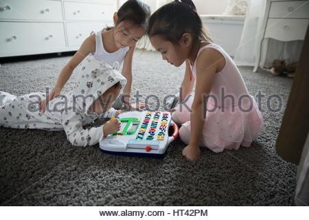 Schwestern und Bruder Alphabet Spiel auf Teppich im Schlafzimmer - Stockfoto