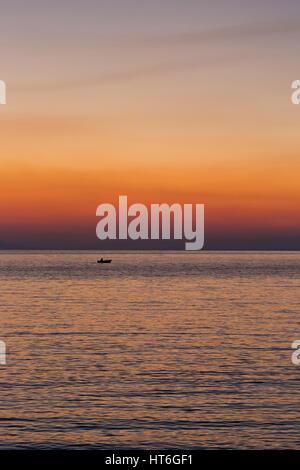 Kleines Boot Sonnenuntergang Silhouette ist ein Fischerboot paddeln entlang des Wassers mit einem bunten lila und - Stockfoto