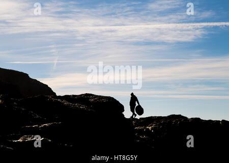 Ein Freiwilliger zu Fuß entlang der Reling Kirche Cove Küste sammeln Müll - Stockfoto