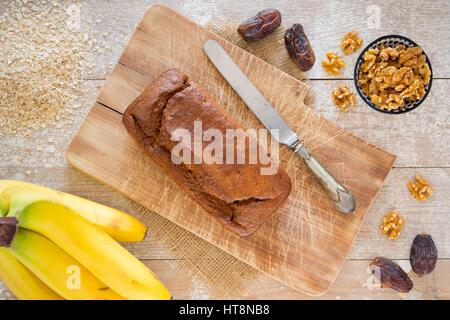 Hausgemachte Bananenbrot mit Walnüssen und Termine auf einem rustikalen Tisch. Stockfoto