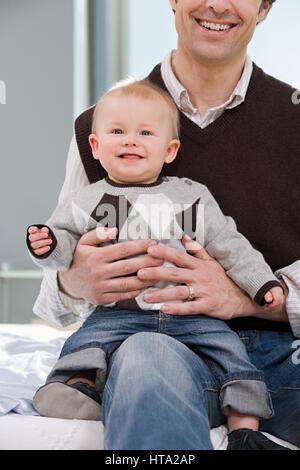 Baby Junge saß auf seiner Väter Knie - Stockfoto