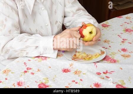 Hände der alten Frau einen Apfel schälen. - Stockfoto