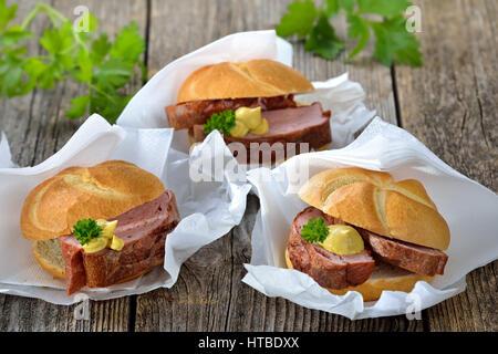 Bayerischen Speisen zum mitnehmen: drei Rollen mit gebackenen Leberkäse und Senf auf Packpapier mit einer Serviette