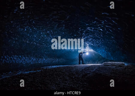 Ein Mann erforscht einen dunklen Tunnel unter dem Eis des Canwell-Gletschers in die Alaska Range. - Stockfoto