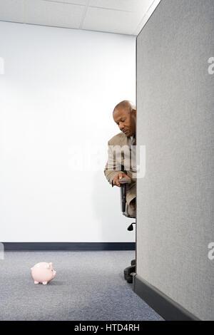 Geschäftsmann, Blick auf ein Sparschwein - Stockfoto