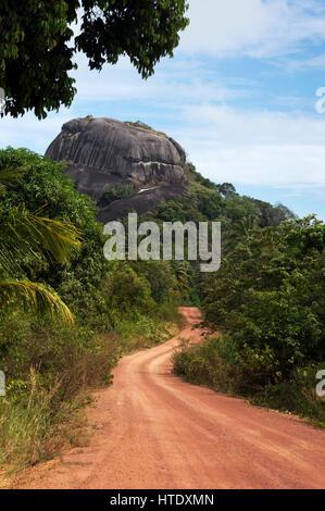 Staubige Straße durch grüne farbige Büsche führt zu einem großen schwarzen Felsen mittags und niemand um ihn herum - Stockfoto