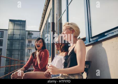 Schuss von lächelnden jungen Freundinnen zusammen auf der Terrasse sitzen. Gemischtrassig Frauen im Freien entspannen und Spaß haben.