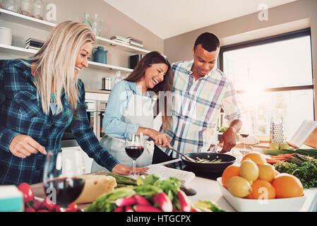 Portrait von drei Personen in der Küche kochen und Spaß dabei haben - Stockfoto