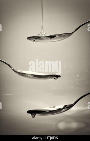 Honig vom Löffel vor einem hellen Hintergrund gießen - Stockfoto