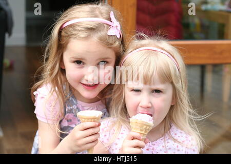 Mädchen blonde Kinder essen lecken lecken Eis Kegel auf einem Sommertag süße Kinder genießen Eis Kegel glücklich - Stockfoto