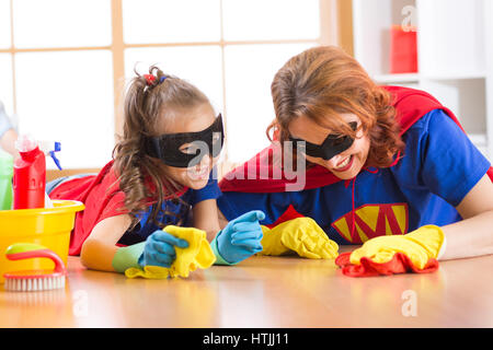 Nette Frau und Tochter Kind gekleidet wie Superhelden Reinigung des Bodens und lächelnd - Stockfoto