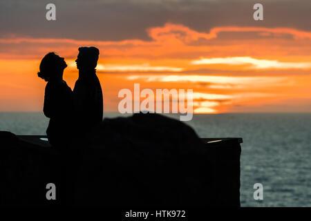 Aberystwyth Wales UK, Sonntag 12. März 2017 UK Wetter: ein junges Paar umarmen und küssen, während hinter ihnen die Sonne spektakulär über den Wassern der Cardigan Bay aus Aberystwyth an der Westküste von Wales untergeht. Foto Credit: Keith Morris/Alamy Live-Nachrichten