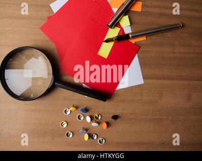 Bunte Briefbögen mit Reißnägel, einen Füllfederhalter und eine Lupe auf einem hölzernen Hintergrund - Stockfoto