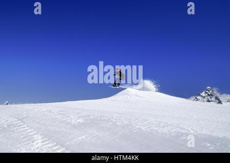 Snowboarder springen im Snowpark im Skigebiet auf Sonne Wintertag. Kaukasus-Gebirge, Region Dombay. - Stockfoto