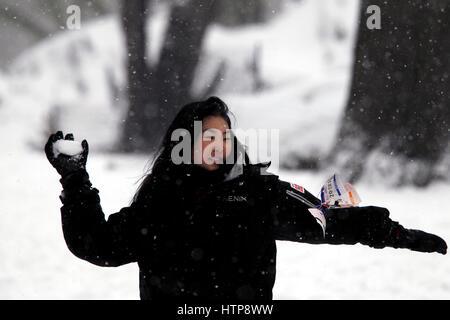 New York, Vereinigte Staaten von Amerika. 14. März 2017. Eine Frau wirft einen Schneeball an ihr Begleiter im New - Stockfoto