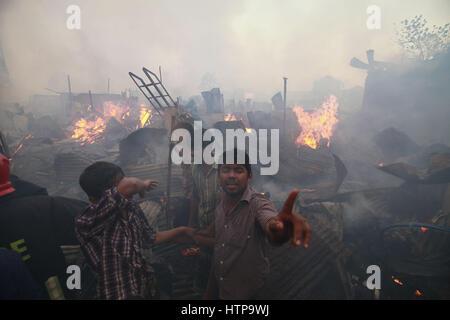 Dhaka, Bangladesch. 16. März 2017. Slumbewohner trat die Feuerwehr nach Flammen an einem der größten Slums in der - Stockfoto