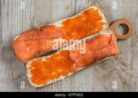Sandwiches mit rotem Kaviar und Lachs auf hölzernen Hintergrund - Stockfoto