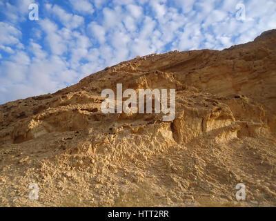 Sandy Klippe gegen den blauen Himmel mit Wolken - Stockfoto