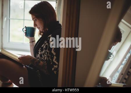 Frau mit Kaffee und einem Buch sitzend am Fensterbrett - Stockfoto
