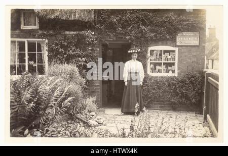 Edwardian Postkarte der Dame Ladenbesitzer, außerhalb ihres ländlichen Dorf Shop, Waren im Fenster, bei ihrem Haus, - Stockfoto