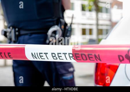 Niederländische Polizei Linie nicht überqueren. Roter Kunststoff Klebeband und Polizist, Pistole Gürtel, Handschellen - Stockfoto