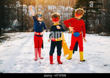Drei Kinder stehen auf zugefrorenen See in Superhelden-Kostümen - Stockfoto