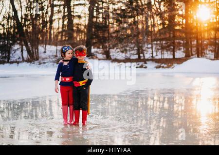 Jungen und Mädchen stehen auf zugefrorenen See in Superhelden-Kostümen - Stockfoto