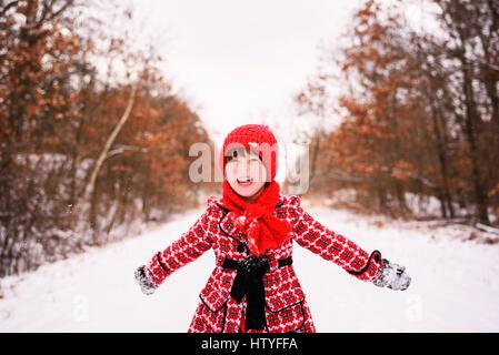 Mädchen stehen im Winterwald mit ausgestreckten Armen - Stockfoto