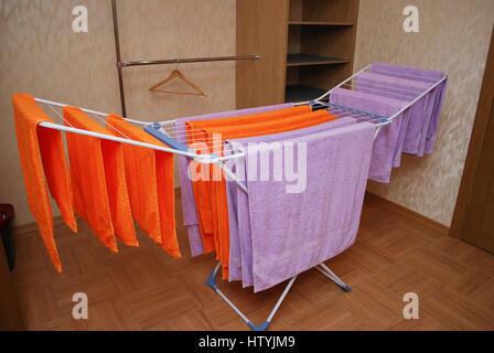 Handtücher von lila und orange farbe trocknen auf ein metall
