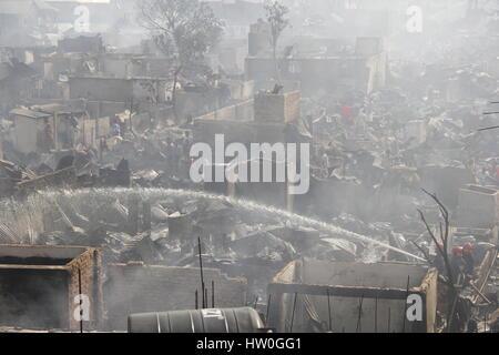 Dhaka. 16. März 2017. Foto aufgenommen am 16. März 2017 zeigt Feuerwehrmänner Besprühen mit Wasser in den Slums - Stockfoto