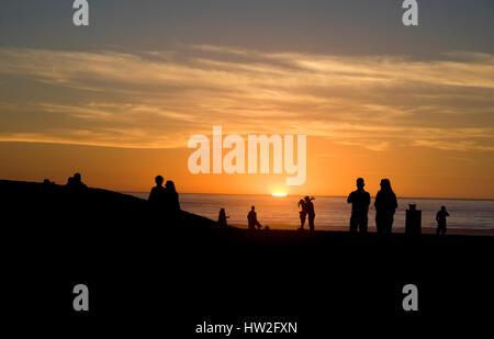 Ein paar umarmt am Strand als die Sonnenuntergänge am Venice Beach, Kalifornien - Stockfoto