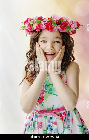 Porträt von überrascht, kleines Mädchen in schönen Frühling Kleid mit Blumen-Kranz auf Kopf, Gefühle zeigen - Stockfoto
