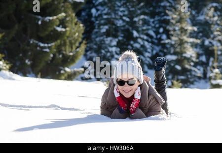 Fröhliche Frau, die Spaß im Schnee lag mit roter Wolle Handschuhe und Sonnenbrille - Stockfoto
