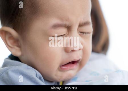 Porträt von 5 Monaten asiatisches Baby junge weinend im Arm der Mutter. - Stockfoto