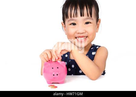 Asiatische kleine chinesische Mädchen setzen Münzen ins Sparschwein isoliert auf weißem Hintergrund - Stockfoto