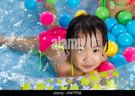 Asiatische chinesische Mädchen spielen in einen aufblasbaren Kautschuk-Swimmingpool im freien - Stockfoto
