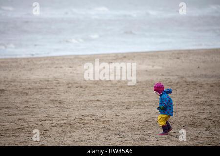 North Wales, UK 18. March2017, nassen und windige Bedingungen als Strand Partygänger wickeln für einen nassen und - Stockfoto