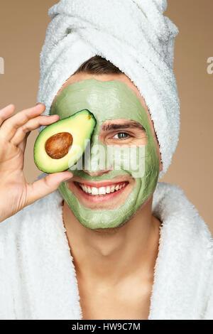 Gut aussehender Mann hält eine halbe Avocado in der hand. Foto des Mannes mit feuchtigkeitsspendenden Gesichtsmaske. - Stockfoto