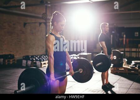Zwei muskulöse Jugendliche im Fitnessstudio Hanteln mit Arme heben. - Stockfoto