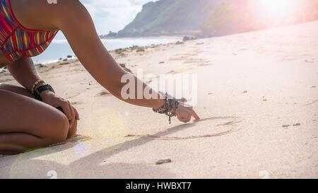 Junge Frau Zeichnung Herzform im Sand am Strand, Bali - Stockfoto
