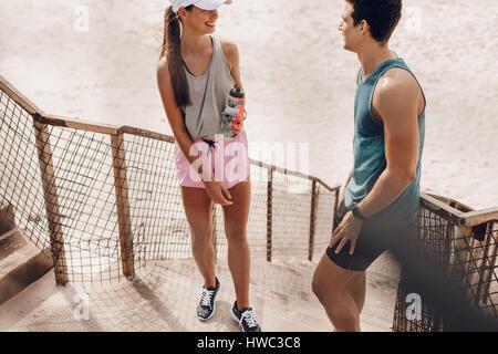 Im Freien Schuss junger Mann und Frau sich nach Morgenlauf am Strand ausruhen. Paar, entspannend und sprechen während - Stockfoto