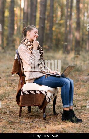 Interessant, attraktiv, niedliche Mädchen mit Bob in den Haaren, im warmen Pullover und Schal auf Stuhl in den herbstlichen - Stockfoto