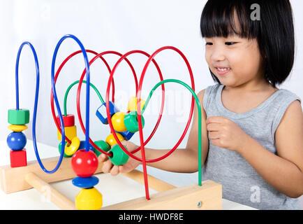 Asiatische kleine chinesische Mädchen spielen bunte Bildungs-Spielzeug in isolierten weißen Hintergrund - Stockfoto