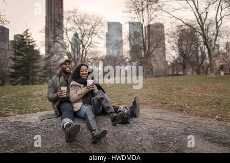 Paar sitzt auf Felsen im Park mit Kaffee zum mitnehmen - Stockfoto