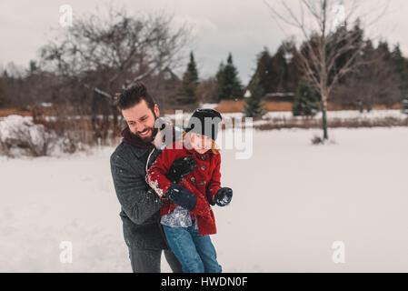 Vater und Tochter spielen im Schnee - Stockfoto