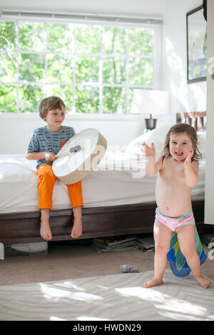 Brother Trommeln auf Bett, Schwester Superhelden zu spielen - Stockfoto