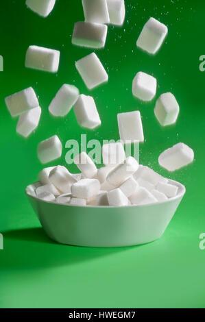 Zucker aus Schüssel auf grünem Hintergrund schweben - Stockfoto