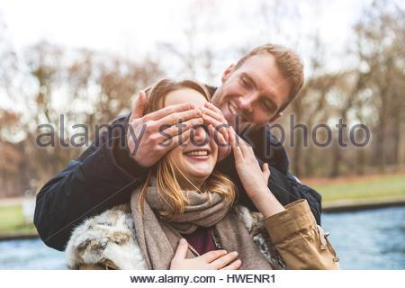 Junger Mann Bedeckung Freundin Augen am Park am Flussufer - Stockfoto