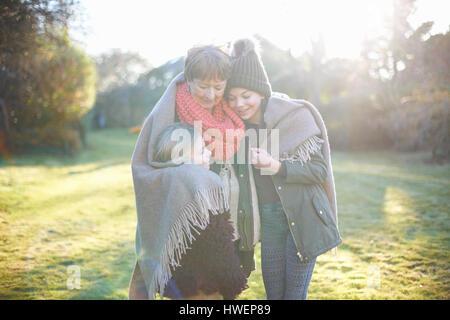 Großmutter und Enkelinnen umarmt im Garten - Stockfoto